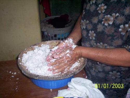 Espremendo o coco para retirar o leite